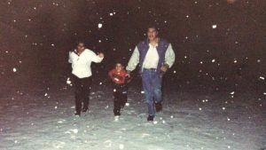 Young Oscar and parents running through the snow