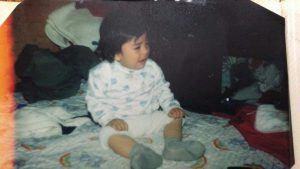 Baby Oscar sitting on a bed