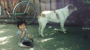 Young Oscar playing by a dog